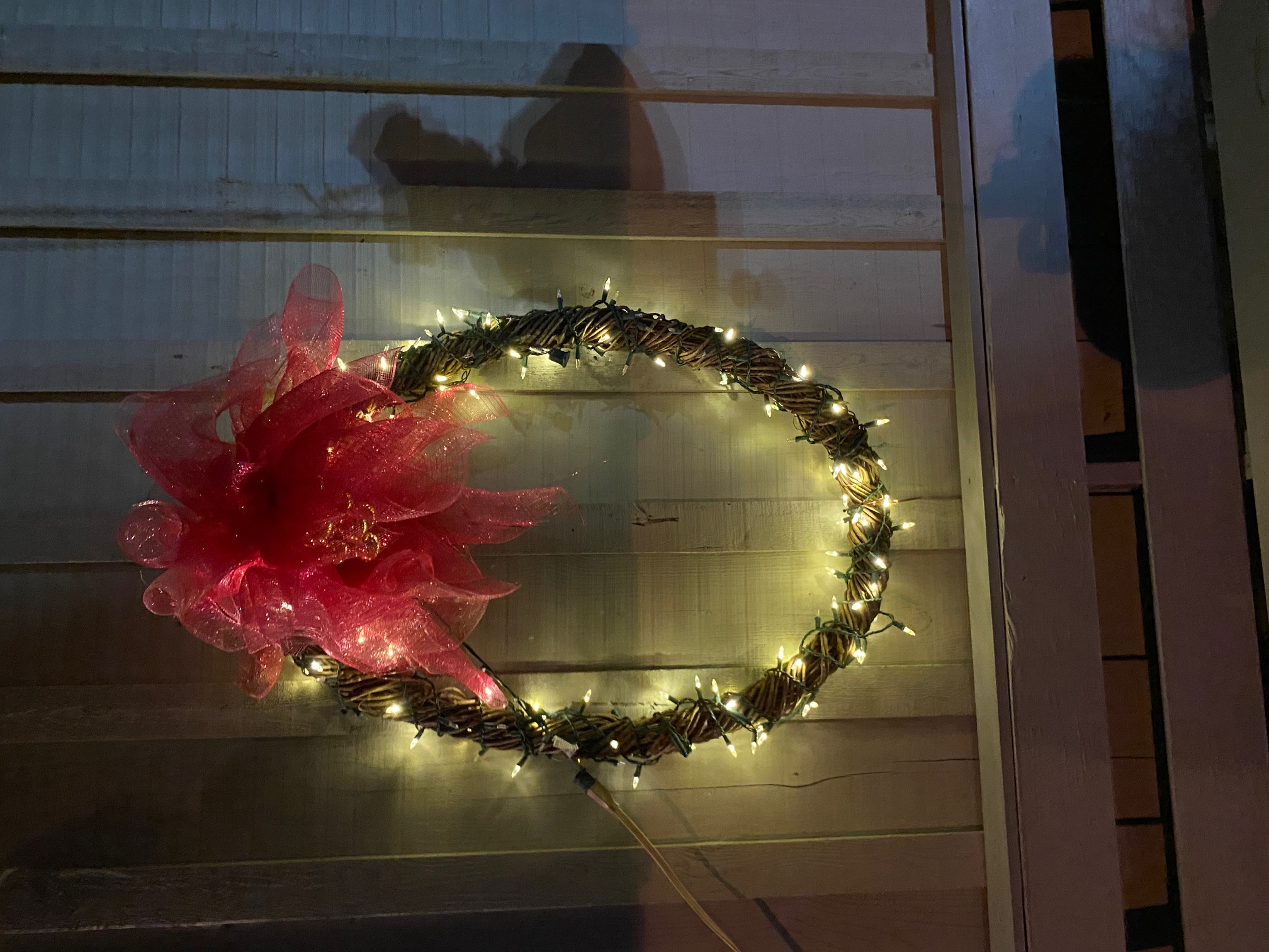 A lit wreath with red bow.