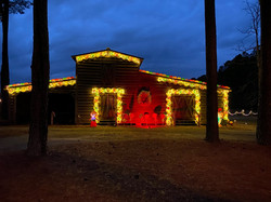 Gingerbread pack house at night time with lights on.