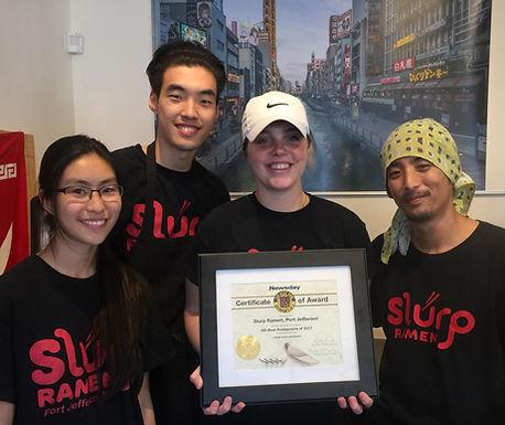Four Slurp Ramen teammates holding an award