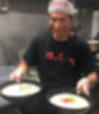 A ramen chef in a restaurant kitchen carrying to bowls of ramen