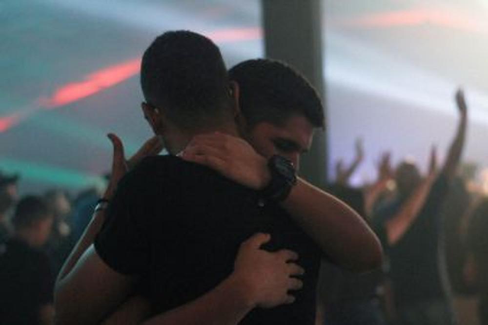 Two men hugging.
