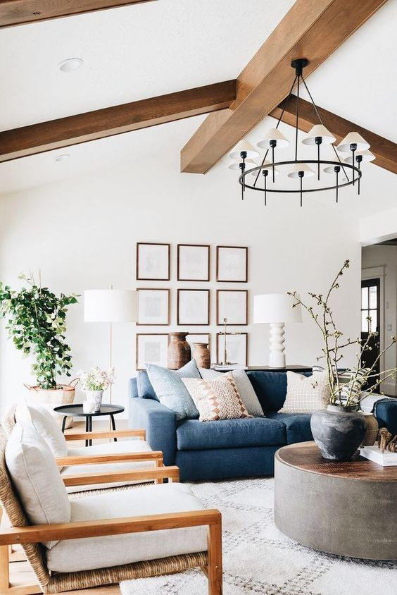 Photo of a beautiful living area with blue velvet sofa and beams on the ceiling