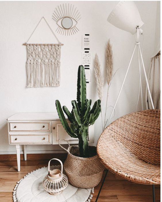 Boho chic living area from Interior Connection. Image shows traditional cabinet, pot plant, macrame wallhanging and rattan armchair.