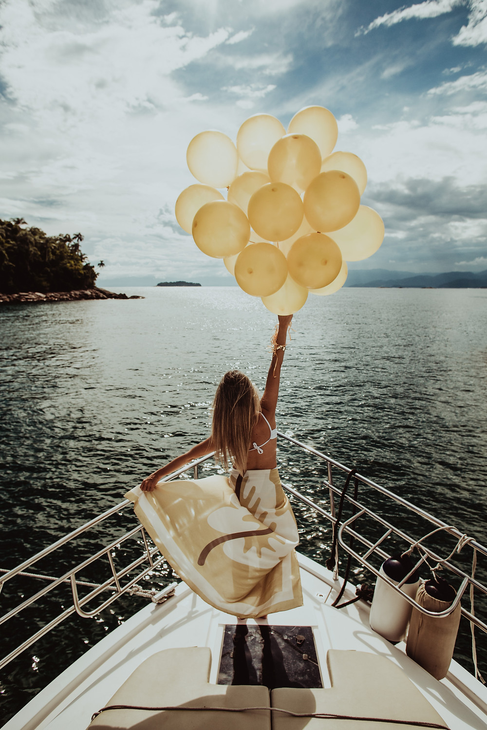 Beautiful woman holding up a bunch of balloons on a yacht.