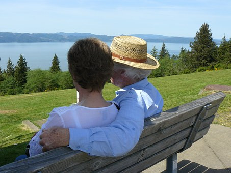 Elderly couple sitting on bench in front of a view of the water.