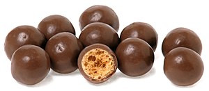 A pile of Maltesers candies and one split in half.