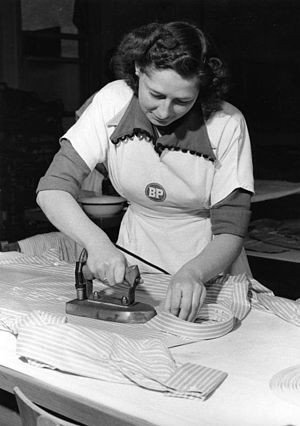 Woman ironing a shirt (Köln, Germany 1953).