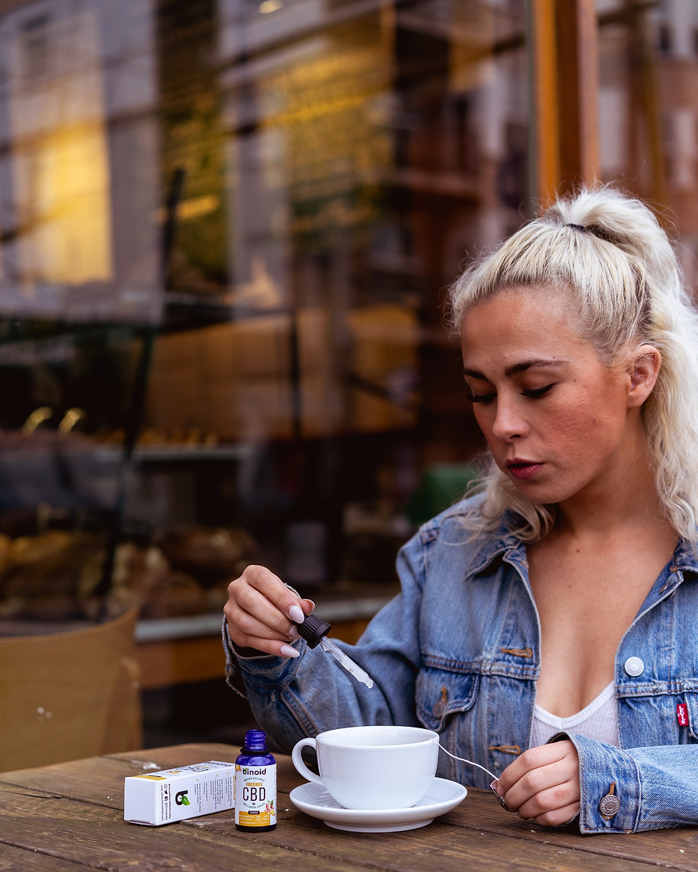 Woman drops CBD into her beverage at a cafe