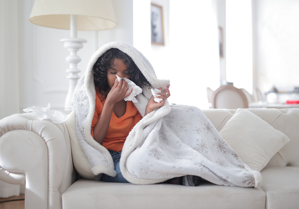 Women blowing her nose on the couch