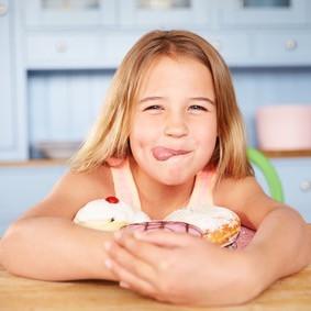 Kind sitzt am Tisch mit süßen Leckereien.