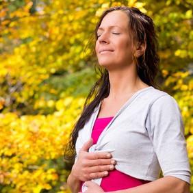 Frau atmet bewusst in den Bauch