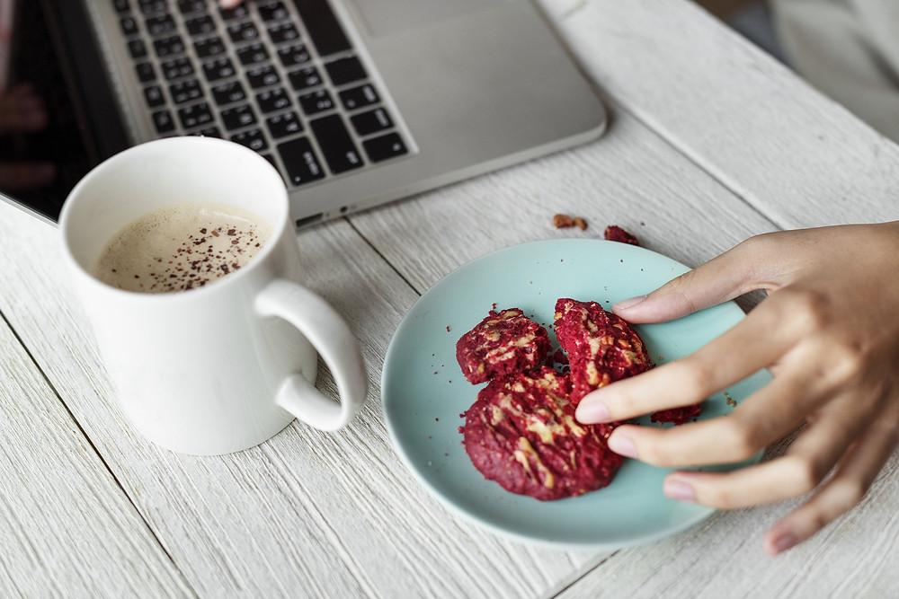 Frau isst am Schreibtisch hastig eine Portion Nudeln.