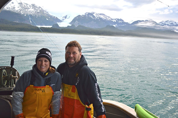 Mark and Dawn, the owners of Sitka Wild Seafoods posing for a picture with beautiful alaskan scenery