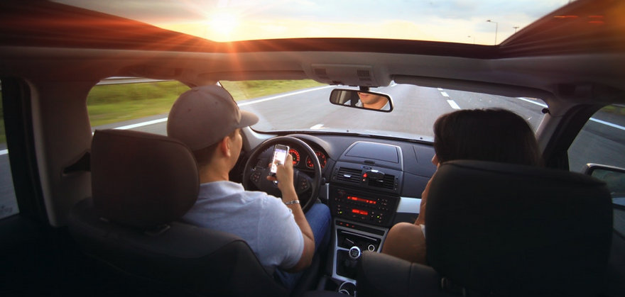 Fahrer spielt mit Handy im autonom fahrenden Auto statt zu lenken
