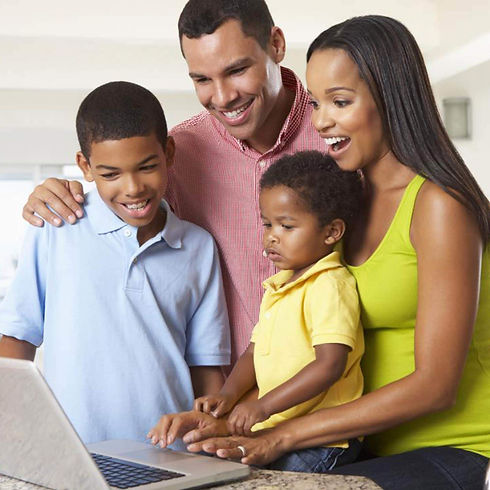 Family of four looking at a laptop with big smiles on their faces