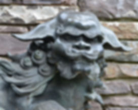 Japanese Bronze Shi Shi Dog in front of a stone wall