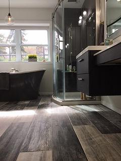 floating vanity, freestanding tub, wood tile,curved shower glass