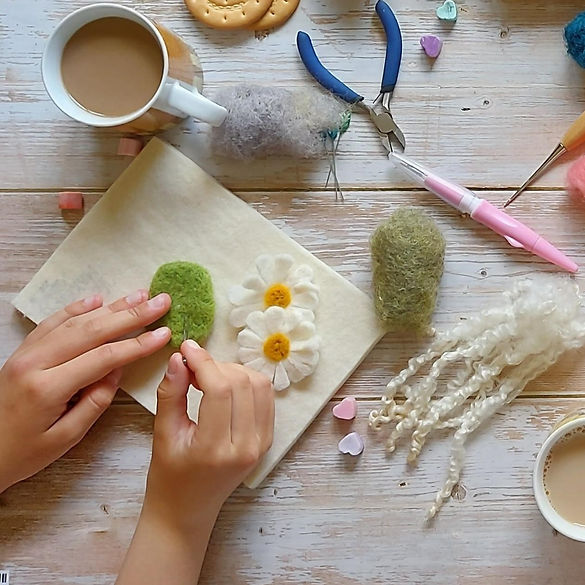 Hands needle felting with tools and wool. Group needle felting classes/workshops