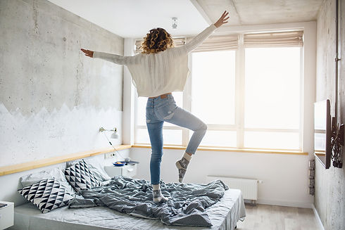 young-happy-woman-jumping-on-bed-in-morn
