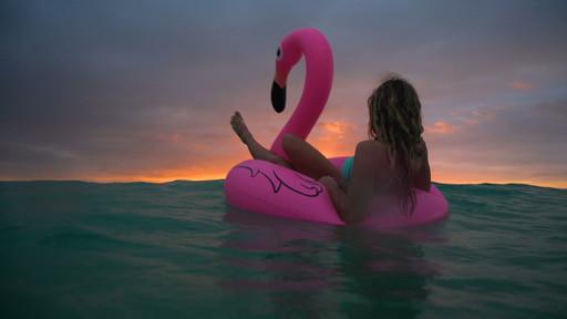 Beautiful girl swimming inflatable flami