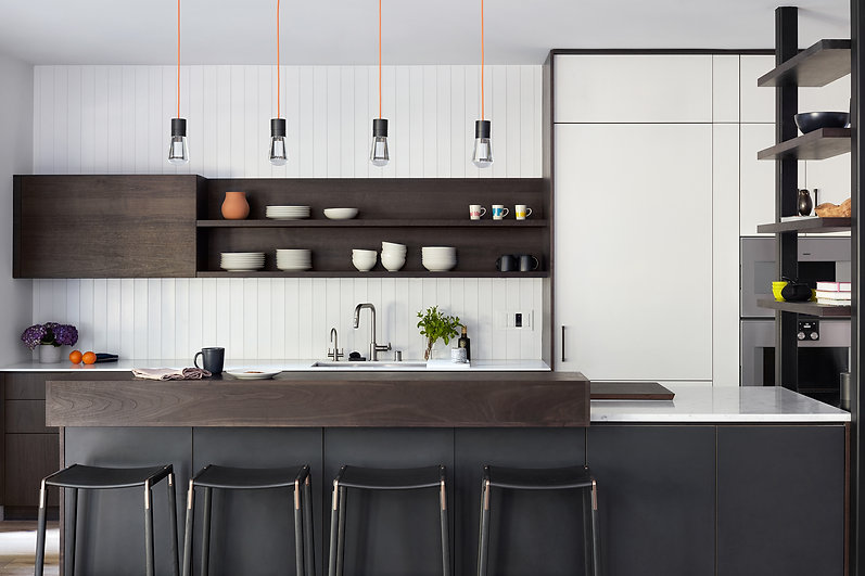 Modern Henrybuilt kitchen in San Francisco Bay Area Menlo Park home. Interi r Design by award-winning Hills & Grant Interior Design. This kitchen has white wall paneling, a dark wood floating cabinet, an island with black laminate cabinets and bar block.