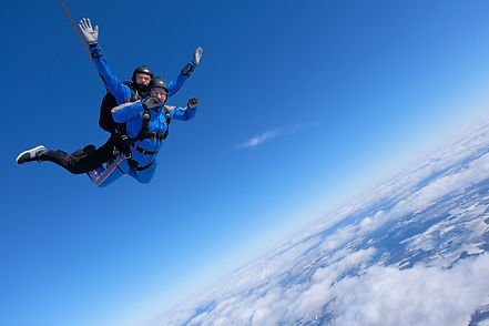 Two guys are jumping a skydiving tandem.