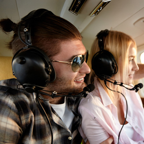 Happy young couple flying in airplane on