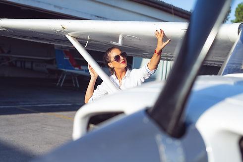 Beautiful female pilot in the hangar doi