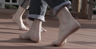 Image of man and woman's bare feet walking across lanai premium decking planks