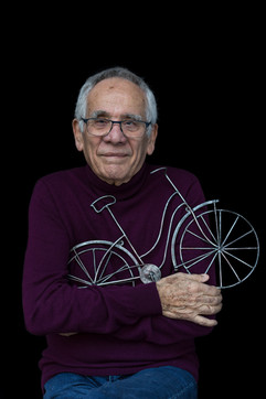 """Erich Reich Sir b. 1935 Vienna, Austria Arrival in UK: 1939  OBJECT: Wire bicycle  """"I organized my first charity bicycle event in 1992. The charity events enabled me to give something back to the UK for allowing me in as an unaccompanied child refugee [on the Kindertransport]. The bicycle events which I organized helped the charities that benefitted thousands of people afflicted with various illnesses. They also challenged the participants physically."""""""