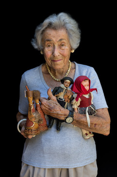 """Margit Meissner b. 1922 Innsbruck, Austria Arrival in USA: 1941  OBJECTS: Dolls  """"These dolls were acquired on the many trips my husband and I took. The black one is an Argentine gaucho — the first one in the collection of some 200 dolls from 50 or so countries. The doll collection represents years of travel and learning about various cultures."""""""