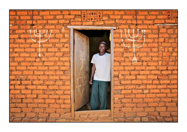 -- Abayudaya Jews --  Joseph Mwanika in the doorway of a house.  Nalubembe Village, Kikubu District, Uganda.