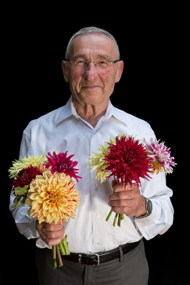 """Nat Shaffir b. 1936 Iași, Romania Arrival in USA: 1961 (via Israel)  OBJECTS: Dahlia flowers (home grown)  """"I grew up on a farm, so gardening was always in my blood. In Romania and Israel, I had mainly vegetable gardens, but after I settled in the United States, I started growing flowers. I grow some 70 varieties of dahlias in my garden. They are a challenging flower to grow because they require specific conditions. I also grow other flowers such as zinnias. Being in nature makes me feel great."""""""