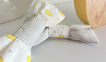 Zoom sur un lot de 2 barettes noeud, mixe jaune et gris d'un motif gouttes et rayures