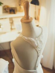 Zoom sur les broderies du dos d'une robe de mariée en cours de montage.