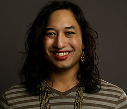 headshot (courtesy of Dena Denny), part of a series of genderqueer and nonbinary folx. i'm wearing a deep red lipstick with shoulder length hair and a gold and silver chain necklace that drops just out of frame. i'm wearing long sleeve t-shirt, gree a horizontally striped shirt, grey-green and brown horizontal stripes