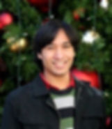 photo of me circa 2013, standing in front of a large christmas tree in Seattle (the tree is only partially visible, with giant gold and red baubles and fairy lights (unlit) visible. my hair is short and i'm wearing a green, grey, an grey-blue thick horizontally striped sweater, a black unzipped jacket over