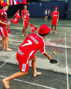 Members of the Swiss team trying out the Swiss game Street Racket for the first time during the Unit