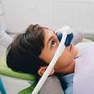 Nitrous oxide is also known as laughing gas. It is often used for children who are mildly or moderately anxious or nervous. It eases their fears so that they can relax during treatment. This helps them to receive treatment in a comfortable and safe manner.  Nitrous oxide is mixed with oxygen and delivered through a small mask over the nose. Your child will be asked to breathe through the nose and not through the mouth. As the gas begins to work, your child usually will become less agitated and less nervous.  The effects of nitrous oxide are mild. It is safe and quickly eliminated from the body. Your child remains awake and can continue to interact with the dentist. When the gas is turned off, the effects wear off very quickly. The dentist will give your child oxygen for a few minutes after treatment. This helps to flush the child's body of any remaining gas.  Sometimes children may reject wearing the mask. Nitrous oxide may not be the right type of sedation for them. In addition, nitrous oxide can sometimes make a child feel nauseous. Before a dental visit, it is best to feed your child only liquids or a light meal a few hours beforehand. Also, if your child is congested or has trouble breathing through the nose on the day of treatment, nitrous oxide may be less effective.