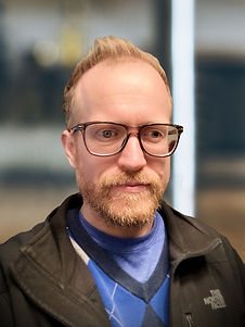 Photo of red headed man with beard wearing black thick rimmed glasses.