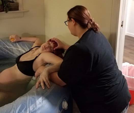 doula applying cool clothes to laboring mothers forehead