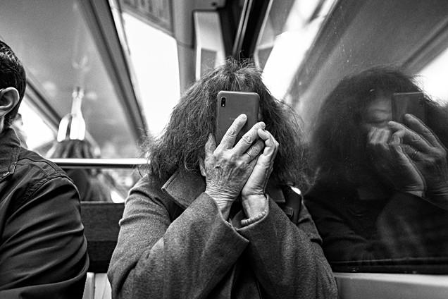 Laurent Delhourme - Dans le métro de paris, une femme est au téléphone, son smartphone est très pret de son visage, nomophobe addicition téléphone, photo laurent delhourme