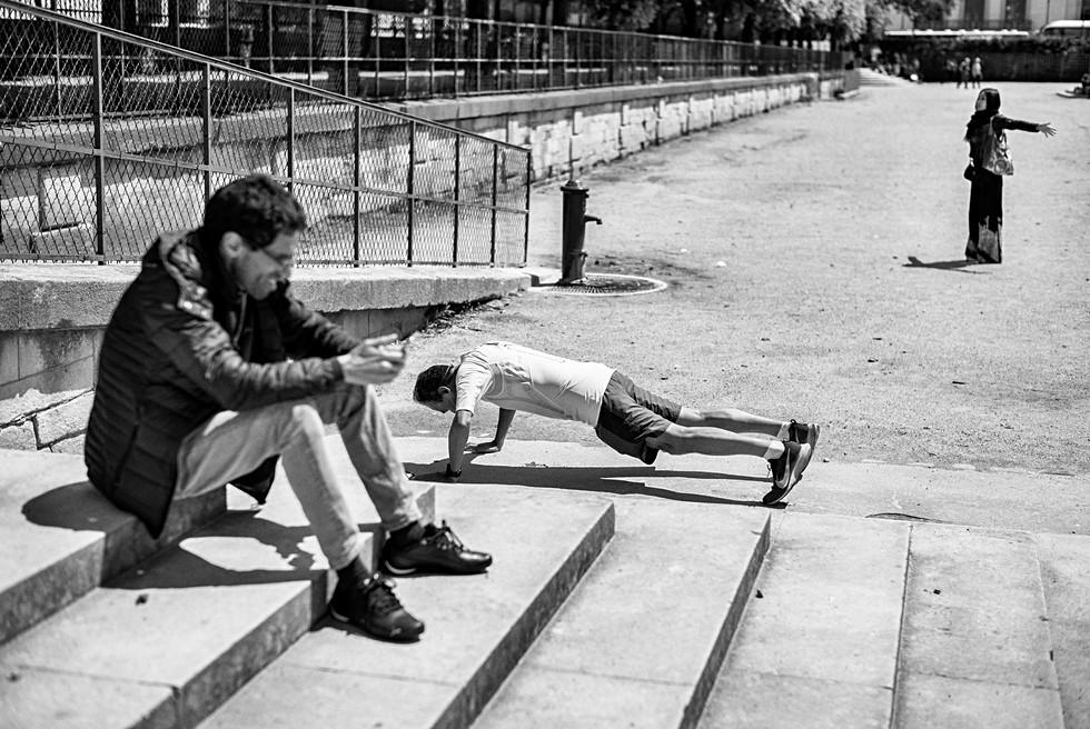 à paris au jardin des tuilleries un homme assi est au téléphone un autre fait du sport et une femme fait des exercices physique, photo de rue par laurent delhourme