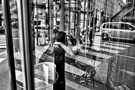 photo taken through a window of a parisian bar where a couple kiss tenderly, there are a lot of reflections on the glass, the photo is in black and white, taken by laurent delhourme french photographer