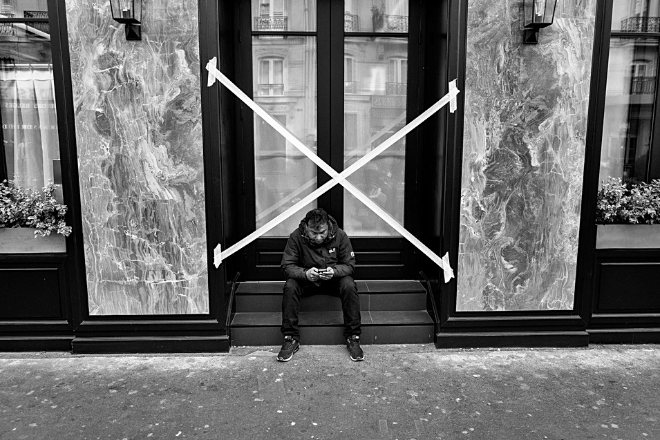 a man sitting on steps in a paris street looking at his phone, nomophobic,