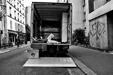 a mover is lying in his truck and consults his cell phone, street photography by laurent delhourme