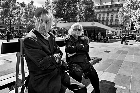 an elderly couple with a protective mask against covid-19 are sitting on a bench place de la republique in paris, humanist photography by laurent delhourme