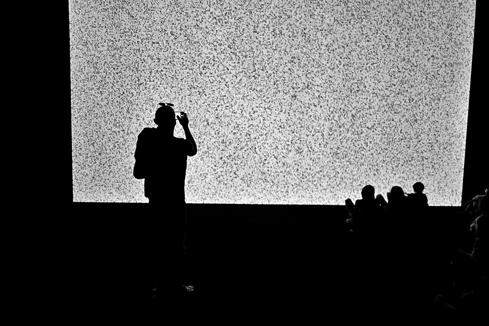 dans une salle de cinéma un homme film l'écran avec son smartphone, nomophobe addicition au téléphone