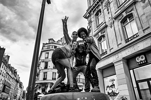 quatre jeunes gens sont sur une poubelle et faitent la victoire de l'équipe de france de football, ils font des gestes vers la camera, ils sont heureux
