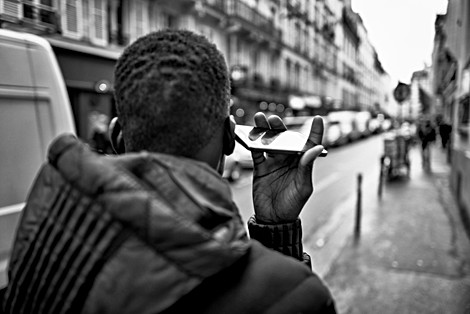 photo in a street in paris, a young boy is on the phone, he walks holding his phone strangely, nomophobia addiction